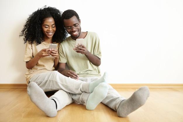 Menschen und moderne technik. lässiges, gemütliches afrikanisches paar, das zeit miteinander verbringt, online einzukaufen oder apps für gadgets zu verwenden, kostenloses wlan zu hause zu genießen und auf dem boden zu sitzen
