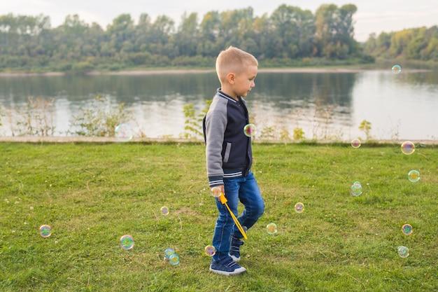 Menschen- und naturkonzept - junge, der mit bunten seifenblasen spielt, die in der luft fliegen.