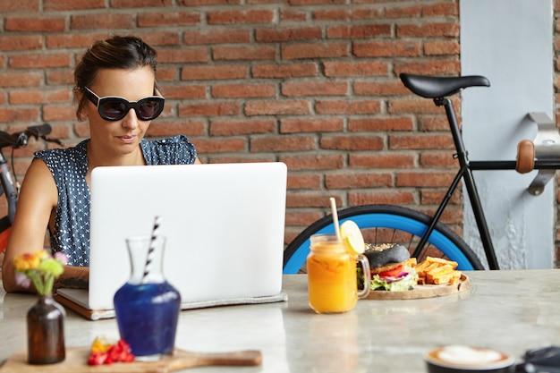 Menschen und technik. ernsthafte und selbstbewusste geschäftsfrau, die lässig mit laptop-pc für fernarbeit gekleidet ist und in der gemütlichen cafeteria mit backsteinmauer sitzt