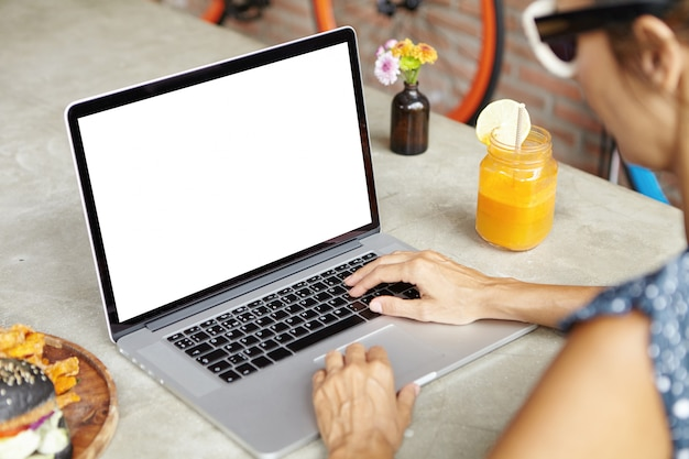 Menschen und technik. frau in den schatten, die internet auf ihrem allgemeinen laptop, tastaturen durchsuchen