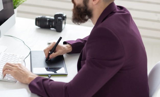 Menschen- und technologiekonzept - erhöhte ansicht eines künstlers, der im büro etwas auf einem grafiktablett zeichnet.
