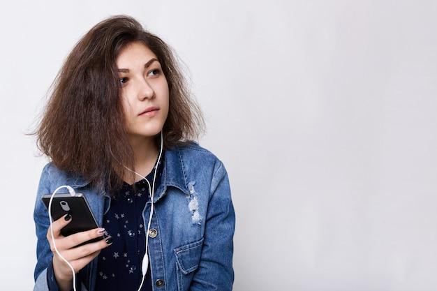 Menschen- und technologiekonzept. mode-lifestyle-porträt einer frau mit haselnussbraunen augen, die eine jeansjacke und einen dunklen rock trägt und der musik zuhört