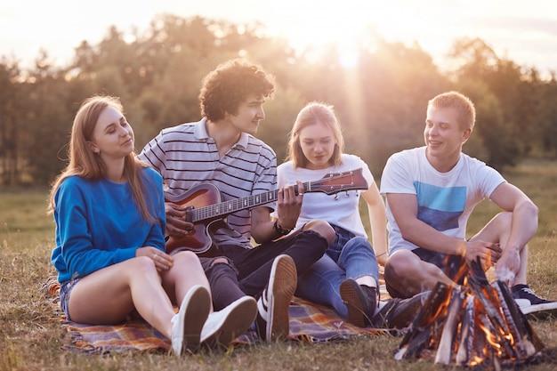 Menschen und urlaubskonzept. fröhliche beste teenager-freunde genießen eine romantische atmosphäre in der natur, machen ein gemeinsames picknick, spielen gitarre, sitzen auf einem plaid in der nähe des lagerfeuers und unterhalten sich freundlich miteinander