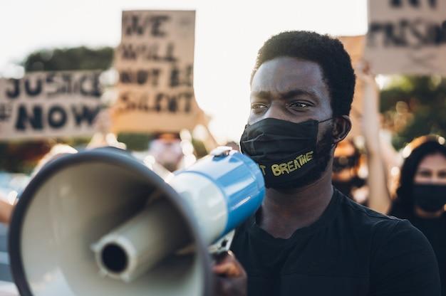 Menschen unterschiedlicher kulturen und rassen protestieren auf der straße für gleiche rechte. schwarze leben zählen