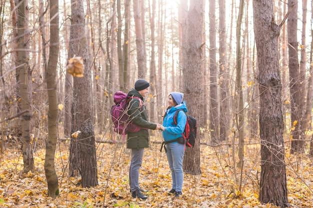 Menschen-, wander-, tourismus- und naturkonzept - paartouristenwandern im herbstwald.