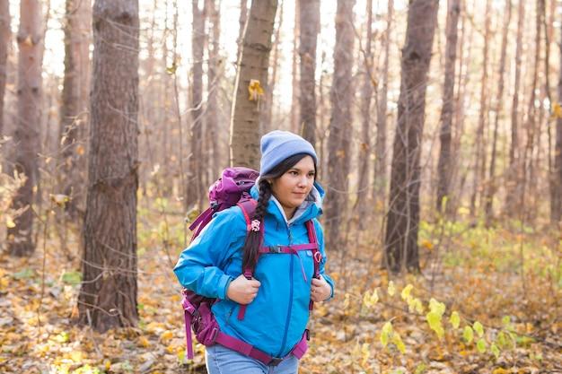 Menschen-, wander- und naturkonzept - touristin, die im herbstwald spazieren geht.