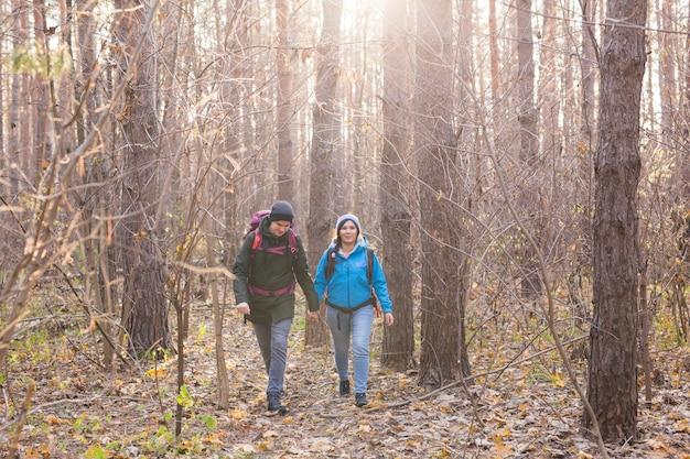 Menschen wandern tourismus und naturkonzeptpaar touristenwandern im herbstwald