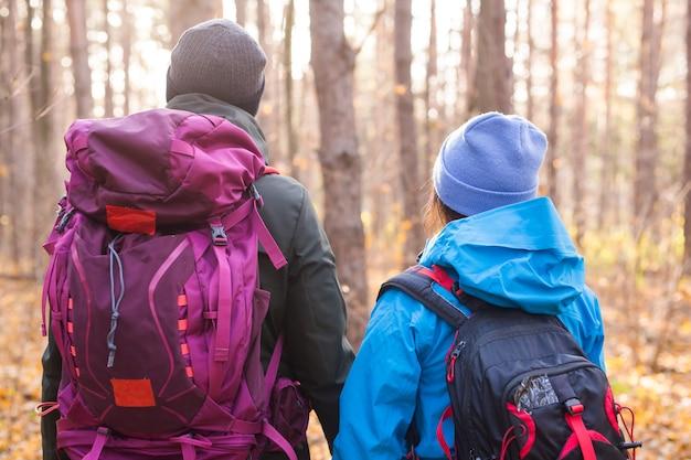 Menschen, wanderung, tourismus und naturkonzept - paartouristenwandern im herbstwald, rückansicht