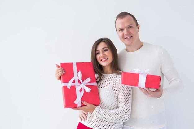 Menschen, weihnachten, geburtstag, feiertage und valentinstag-konzept - glücklicher junger mann und frau mit geschenkboxen auf weißem hintergrund mit kopienraum.