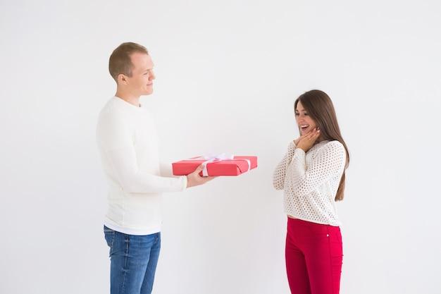 Menschen, weihnachten, geburtstag, feiertage und valentinstag konzept - gut aussehender mann gibt seiner freundin eine geschenkbox auf weißem hintergrund.