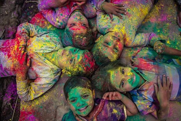 Menschen werfen farben miteinander während der holi-feier im krishna-tempel in nandgaon, indien