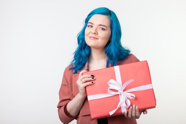 Menschenferien und modekonzept glückliche junge frau mit blauen haaren, die eine geschenkbox auf weiß halten