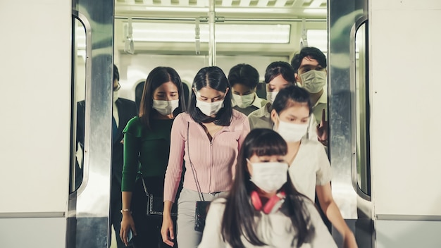 Menschenmenge mit gesichtsmaske auf einer überfüllten öffentlichen u-bahnfahrt
