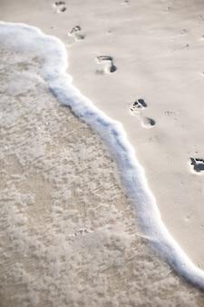Menschliche abdrücke auf weißem sand der karibikinsel