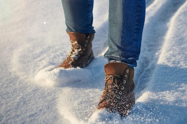 Menschliche beine in bequemen braunen wasserdichten lederstiefeln im neuschnee. lässige mode, trendiges schuhwerk.