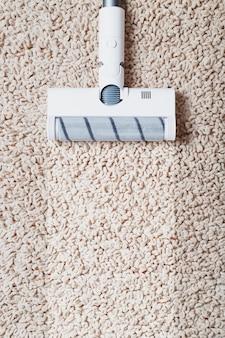 Menschliche beine und eine weiße turbobürste eines akkustaubsaugers reinigen den teppich im haus. moderne technologien für die reinigung.