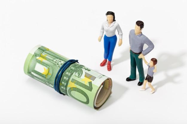 Menschliche darstellung einer familie, die eine geldrolle betrachtet. finanz-, investitions- oder sparkonzept