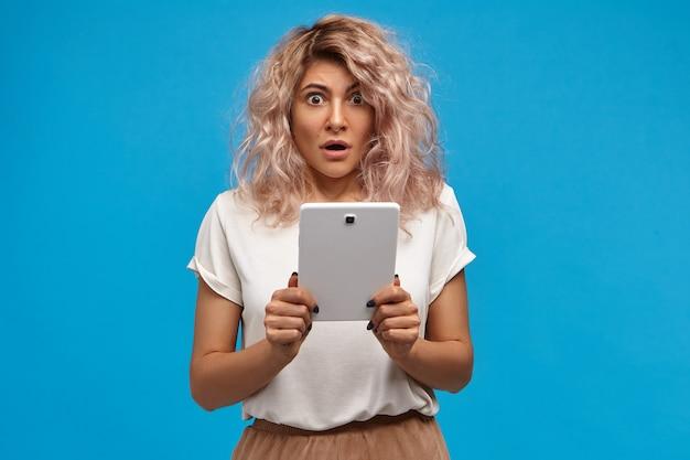 Menschliche emotionen, elektronische geräte und kommunikationskonzept. emotional überraschte junge frau in stilvoller kleidung, die digitales tablett hält und schockierende videoinhalte online ansieht