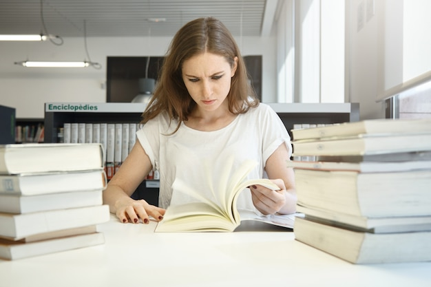 Menschliche emotionen und gefühle. gestresste studentin, die sich auf abschlussprüfungen vorbereitet, in der bibliothek vor großen stapel bücher studiert und auf das lehrbuch starrt