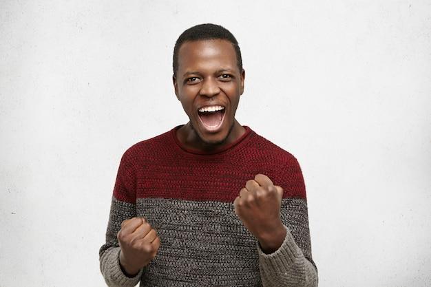 Menschliche emotionen und gefühle. glücklicher glücklicher aufgeregter junger dunkelhäutiger männlicher gewinner, der ausruft, sich über seinen erfolg bei der arbeit freut, ja sagt, fäuste ballt und gleichzeitig seine lebens- und karriereziele erreicht