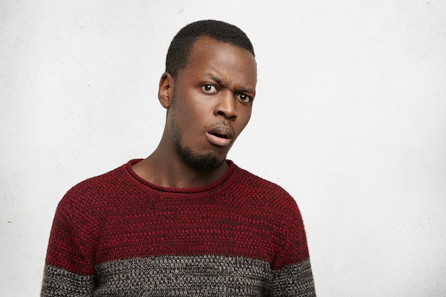 Menschliche emotionen und gefühle. kopfschuss eines bärtigen jungen dunkelhäutigen mannes in jersey-pullover mit gerunzelter stirn, blick, verwirrtem und ahnungslosem gesichtsausdruck. horizontal