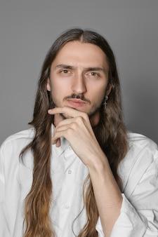 Menschliche emotionen und körpersprache. vertikales bild des stilvollen außergewöhnlichen mannes mit langen braunen haaren und schnurrbart, die hand auf seinem kinn halten