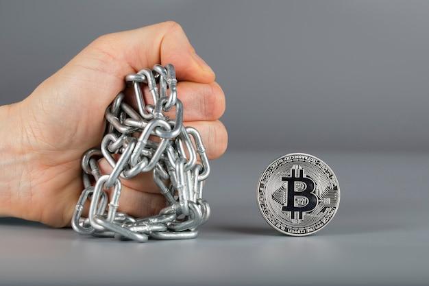 Menschliche faust und bitcoin. nahaufnahme