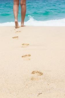 Menschliche fußabdrücke am weißen sandstrand
