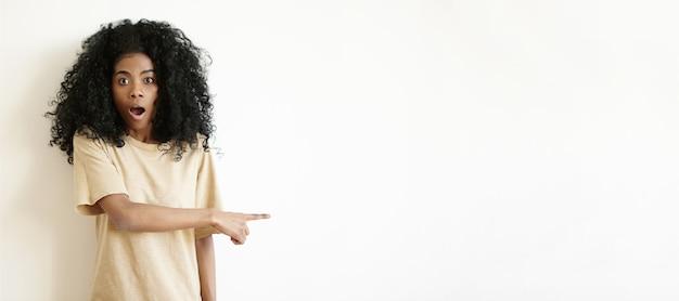 Menschliche gesichtsausdrücke und emotionen. porträt des lustigen überraschten afrikanischen mädchens mit der lockigen frisur, die erstaunt aussieht und ihren zeigefinger auf weiße wand des copyspace zeigt