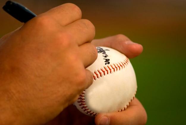 Menschliche hände, die auf ball, nahaufnahme unterzeichnen
