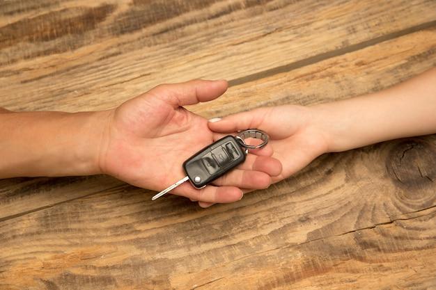 Menschliche hände, die autoschlüssel auf holzhintergrund mit exemplar isoliert halten. verkauf eines transports, vereinbarung, neues auto, leasing für kunden. negativer platz für werbung.