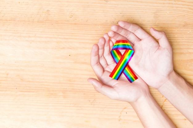 Menschliche hände, die band mit regenbogenflagge halten