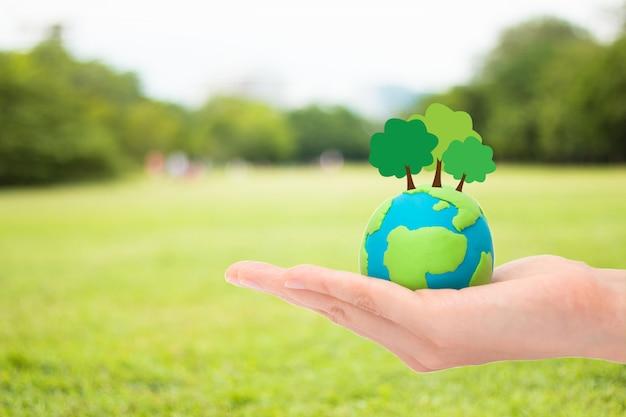 Menschliche hände, die betriebsbäume auf der kugel, dem planeten oder der erde über unscharfem grünem gartennaturhintergrund halten. ökologiekonzept.