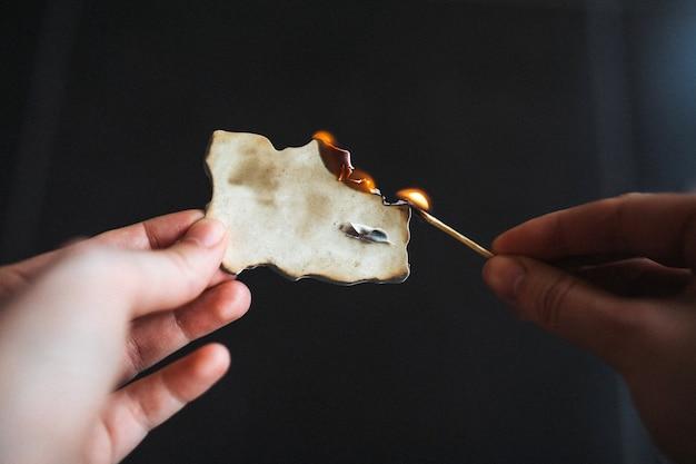 Menschliche hände, die ein altes stück papier in brand setzen.