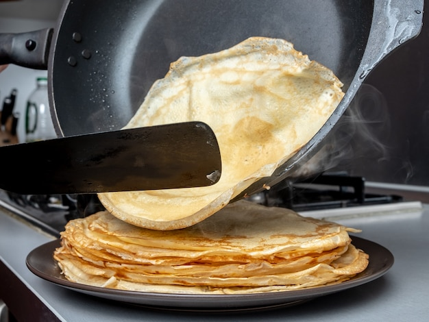 Menschliche hände, die einen spatel und eine pfanne halten, verteilen heißen pfannkuchen auf der schüssel, aus der dampf nach hause kommt küche