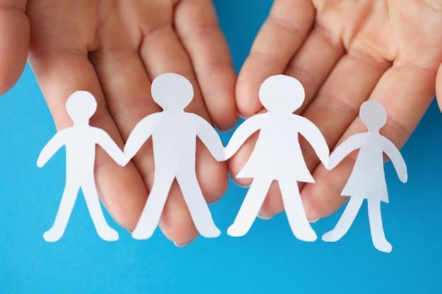Menschliche hände, die figuren von eltern und kindern halten, nahaufnahme des kinderschutztageskonzepts