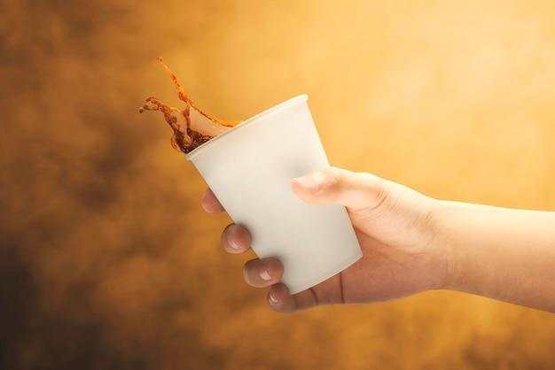 Menschliche hände halten eine tasse kaffee mit spritzern. internationaler kaffeetag