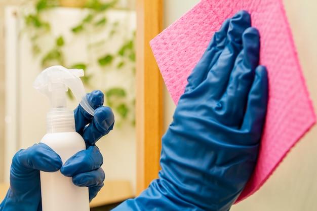 Menschliche hände in schutzhandschuhen desinfizieren die oberfläche mit einem desinfektionsmittel und einem reinigungstuch, um viren vorzubeugen