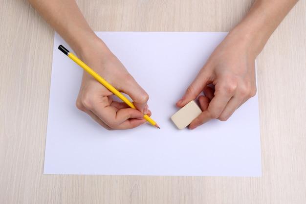 Menschliche hände mit bleistift, der auf papier schreibt und gummi auf holztischhintergrund löscht