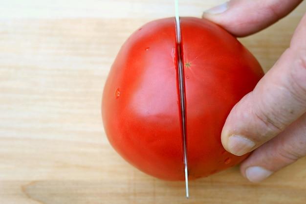 Menschliche hände schnitten rote rosa tomate, mit scharfem küchenmesser, auf holzoberfläche für das kochen.