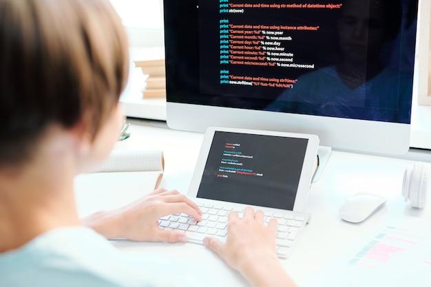 Menschliche hände tippen auf desktop-computertastatur vor monitor und digitalem tablet mit daten