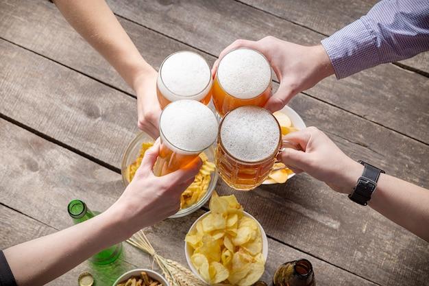 Menschliche hände und gläser bier