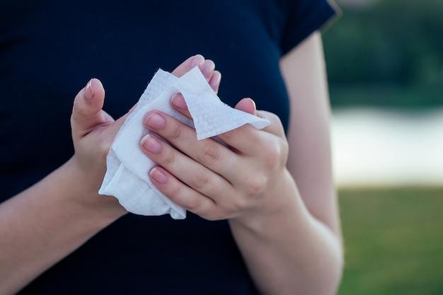 Menschliche hände wischen mit einem nassen serviettenkörperteil ab.