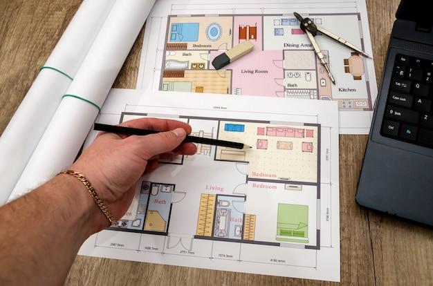 Menschliche hand, architekturplan mit einem laptop