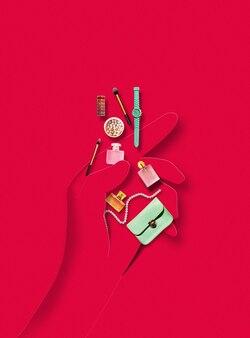 Menschliche hand aus papier mit zubehör und gegenständen für make-up auf rotem hintergrund. zeitgenössische bunte und konzeptionelle helle kunstcollage, modell mit exemplar. schatten, lippenstift, parfüm.