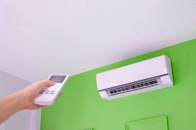 Menschliche hand, die auf fernbedienung für schalter auf klimaanlage drückt.