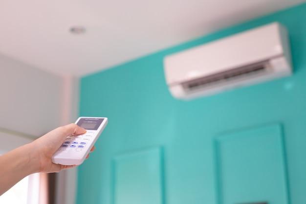 Menschliche hand, die auf fernbedienung zum einschalten der klimaanlage drückt.