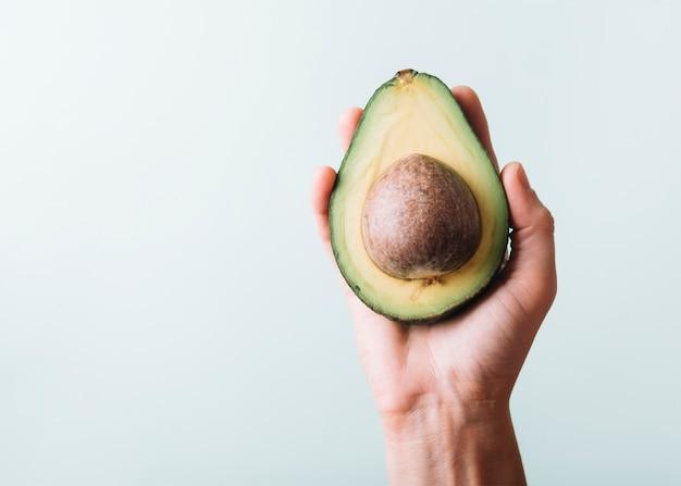 Menschliche hand, die avocado auf grünem hintergrund hält