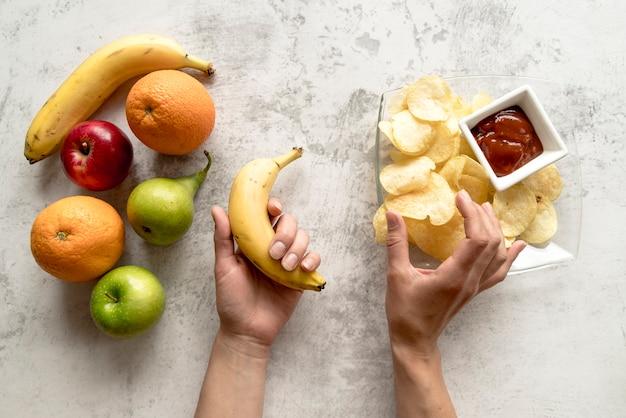 Menschliche hand, die bananen- und kartoffelchips auf zementoberfläche hält