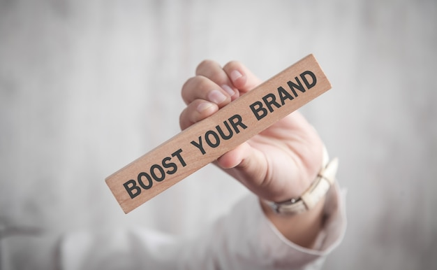 Menschliche hand, die boost your brand-text im geschäftskonzept des holzblocks zeigt